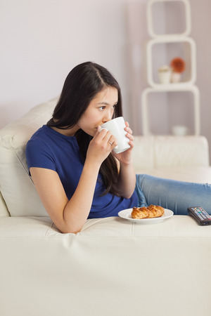 Woman sitting on the sofa drinking coffee with a pastry in living room at home photo