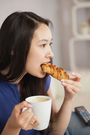 Young asian woman sitting on the sofa having coffee and eating a pastry in living room at home photo