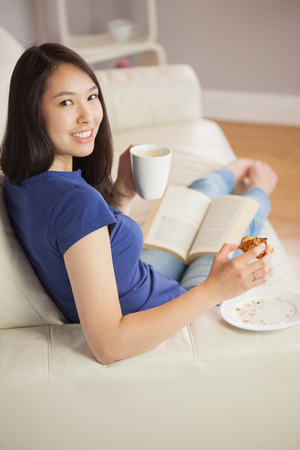 Young woman reading a book and eating pastry with coffee turning to the camera in sitting room at home photo