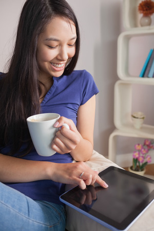Happy asian woman sitting on the couch holding mug of coffee using tablet pc in sitting room at home photo