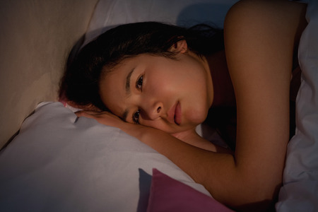 insomnia: Young asian woman suffering from insomnia at home in bedroom Stock Photo