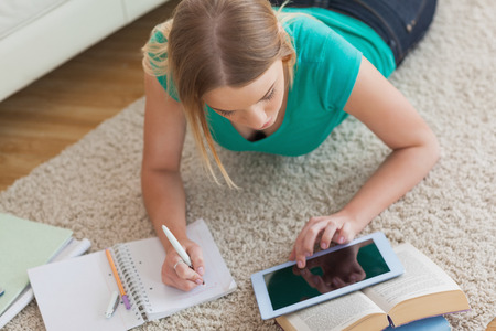 Blonde woman lying on floor using tablet to do her assignment at home in living room photo
