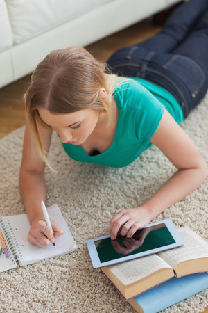 Focused young woman lying on floor using tablet to do her assignment in living room photo