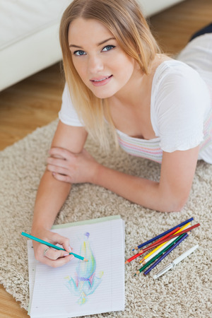 Smiling young woman lying on floor sketching on paper looking at camera photo