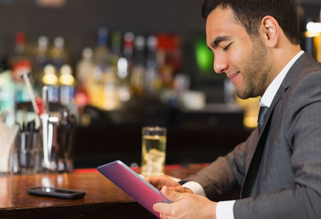 well read: Close up of businessman sitting at bar and reading drinks menu