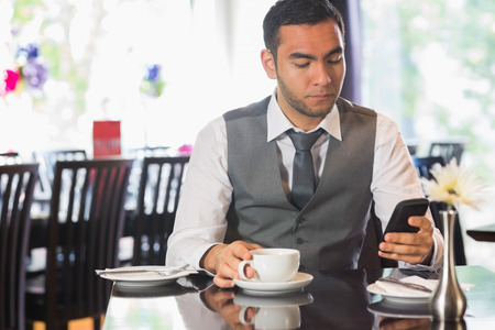 Attractive businessman sitting in restaurant and using his phone photo