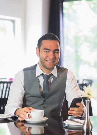 Smiling businessman having coffee and holding phone looking at camera photo