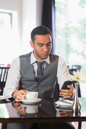Businessman having coffee in restaurant using phone photo
