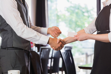swapping: Business team shaking hands and swapping card in a cafe Stock Photo
