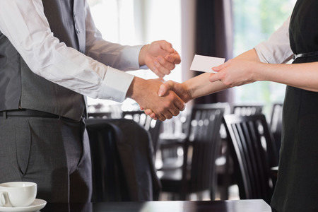 handing: Busines people shaking hands after meeting and changing cards in restaurant
