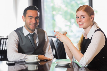 Business people having coffee and looking at camera in a cafe photo