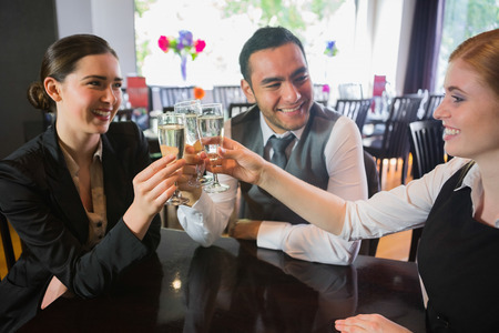 Three business people toasting their success in a restaurant photo