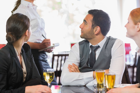 alcohol server: Business people talking to the waiter in the restaurant