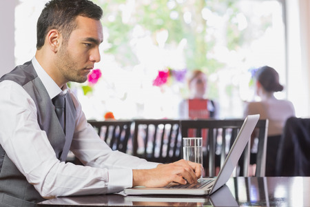 Concentrated businessman working on laptop in restaurant photo