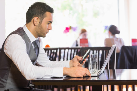 Serious businessman using phone while working on laptop in a restaurant photo