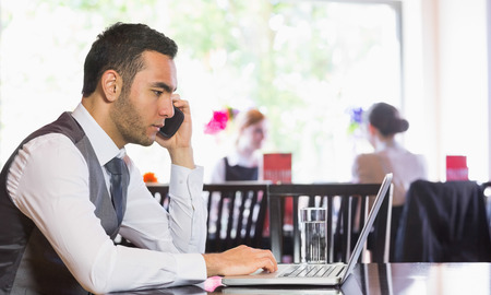 Serious businessman man calling on phone using laptop in a restaurant photo