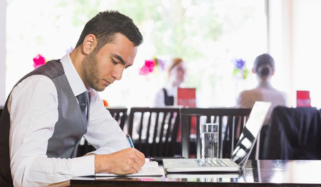 Concentrated businessman writing something in restaurant photo