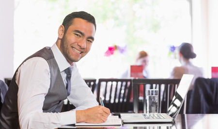 Smiling businessman writing while looking at camera in a restaurant photo