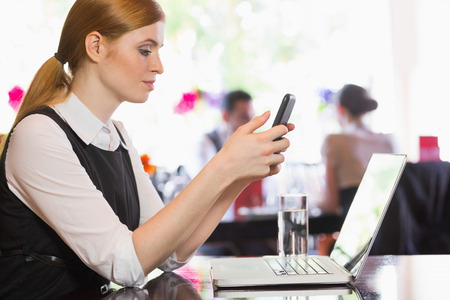Concentrated businesswoman sending a text in a restaurant photo