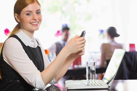 Happy businesswoman sending a text looking at camera in a restaurant photo