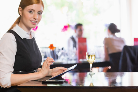 Businesswoman using tablet and looking at camera in a restaurant photo