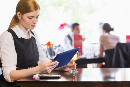 Businesswoman looking at tablet screen while holding wine glass in a restaurant photo