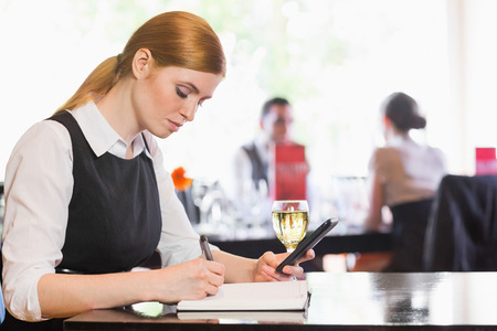 Concentrated businesswoman holding phone while writing in a restaurant photo