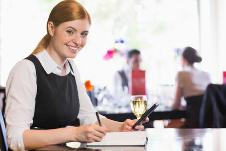 Smiling businesswoman holding phone and writing while looking at camera in a restaurant photo