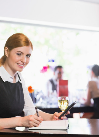 Smiling businesswoman writing and holding phone while looking at camera in a restaurant photo