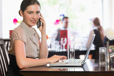 Businesswoman calling on phone using laptop looking at camera in a cafe photo