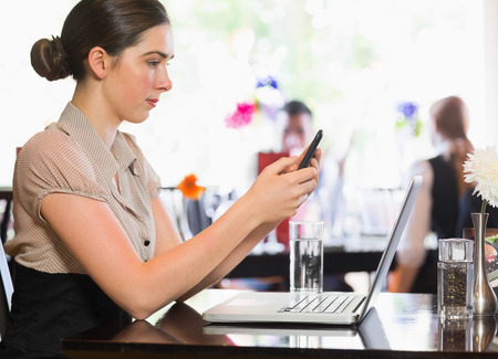 Businesswoman texting on phone in a restaurant photo