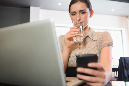Businesswoman using phone while drinking water in a cafe photo