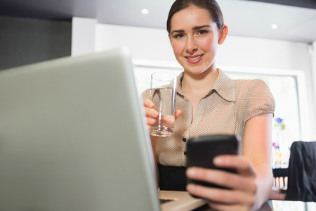 Smiling businesswoman holding glass of water and phone while looking at camera in a cafe photo