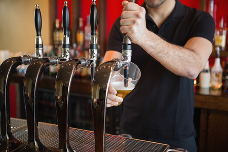 Barkeeper pulling a pint of beer behind the bar Stock Photo