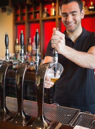 working hour: Handsome barkeeper pulling a pint of beer and smiling behind the bar
