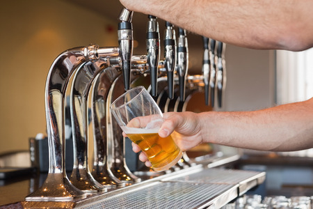 beer tap: Mans hand pouring pint of beer behind the bar