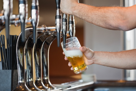 beer pump: Barmans arms pulling a pint of beer behind the bar Stock Photo