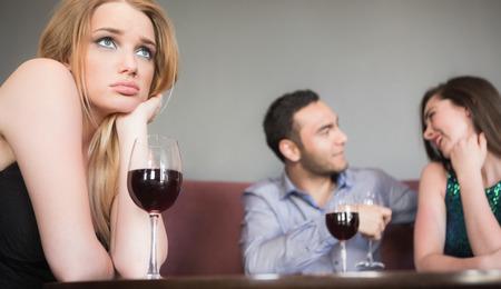 mujer sola: Mujer rubia sintiendo celos de pareja coqueteando junto a ella en un bar