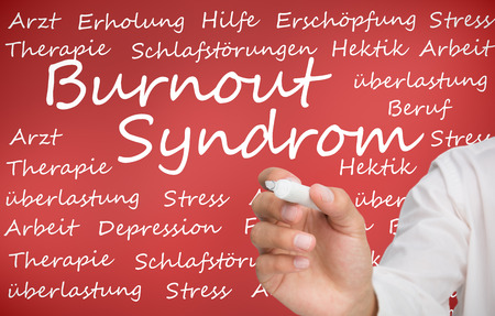 Hand writing different german words about burnout syndrome on red background