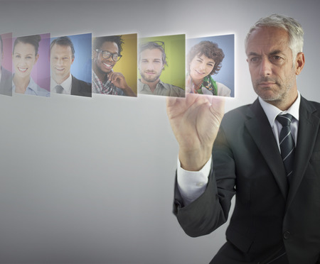 Serious human resources director selecting future employees on digital screen photo