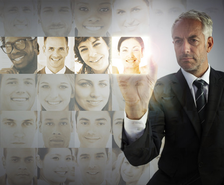 Stern businessman choosing future employees on digital interfaces photo