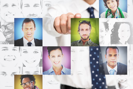 Businessman pointing at digital interface presenting profile pictures on white background photo