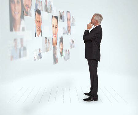 Thoughtful businessman looking at a wall covered by profile pictures on white background photo