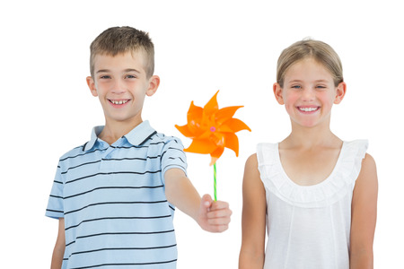 Smiling brother and sister playing with pinwheel on white background photo