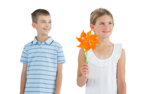 Pensive brother and sister playing with pinwheel on white background photo