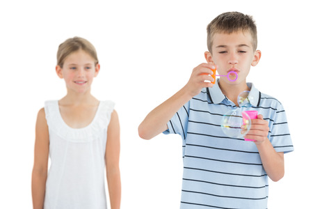 Boy making bubbles while his sister looking at him on white background photo
