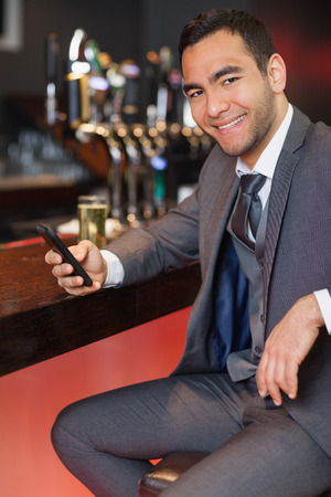 Cheerful businessman sending a text while having a drink in a classy bar photo