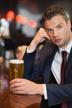 Worried businessman having a drink in a classy bar photo