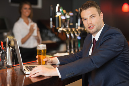 Businessman having a pint while working on his laptop in a classy bar photo