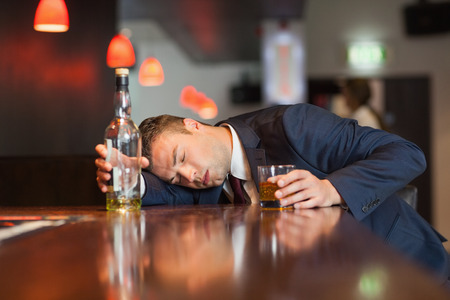 Unmoving businessman holding whiskey glass lying on a counter in a classy bar photo